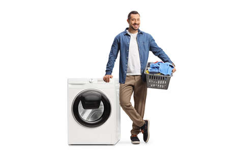 Casual young guy with a laundry basket and a washing machine isolated on white background