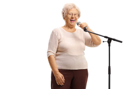 Elderly lady standing in front of a microphone isolated on white background