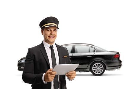 Chauffeur with a digital tablet standing in front of a black car isolated on white background