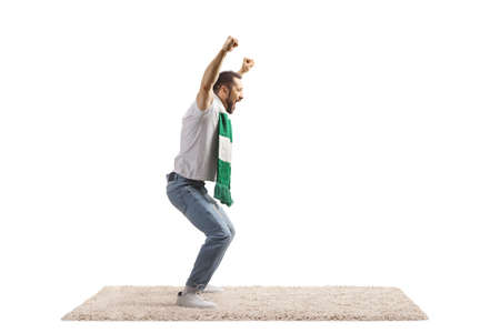 Full length profile shot of an excited young man with a scarf cheering isolated on white background Imagens
