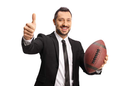 Smiling businessman holding a rugby ball and gesturing thumbs up isolated on white background Imagens