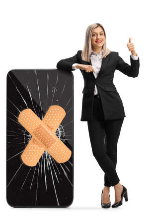 Full length portrait of a businesswoman leaning on a cracked smartphone with bandage and showing thumbs up isolated on white background