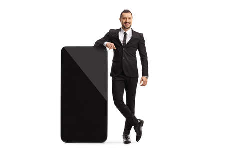 Full length portrait of a businessman standing next to a big mobile phone isolated on white background Imagens