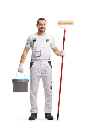 Full length portrait of a painter in a white uniform with a bucket and a paint roller isolated on white background Imagens