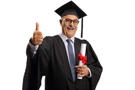 Happy mature man in a graduation gown holding a diploma and showing thumbs up isolated on white background