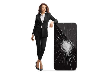 Full length portrait of a young businesswoman leaning on a cracked smartphone isolated on white background