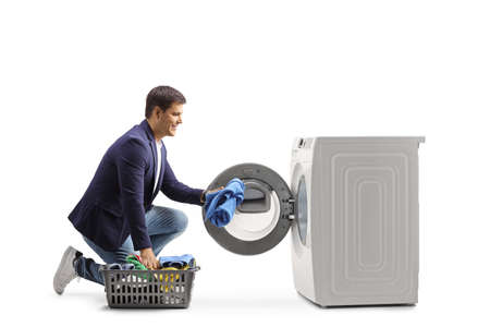 Young man loading a washing machine isolated on white background