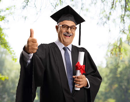 Mature man in a graduation gown holding a diploma and showing thumbs up outdoors