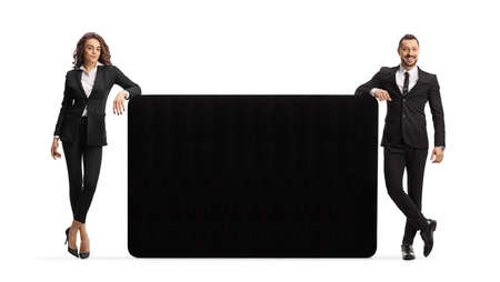 Businessman and businesswoman leaning on a black panel isolated on white background
