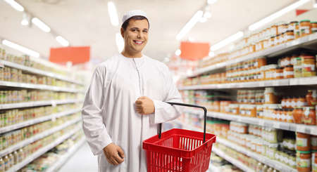 Young man in ethnic clothes holding a shopping basket inside a supermarket Imagens