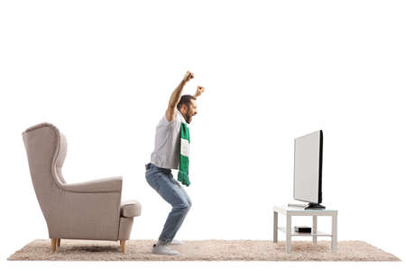 Full length profile shot of an excited young man with a scarf cheering and watching fotball on tv isolated on white background