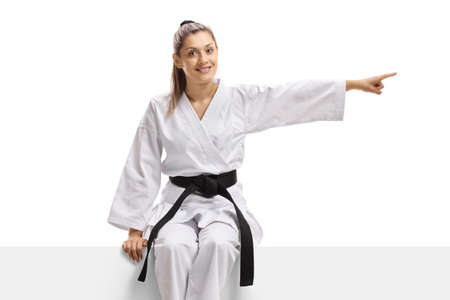 Woman in kimono and black belt sitting on a panel and pointing to the side isolated on white background