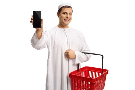 Young man in ethnic clothes holding a shopping basket iand showing a mobile phone isolated on white background Imagens