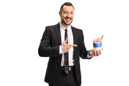 Man in a suit and tie with ice cream in a paper cup pointing isolated on white background Imagens