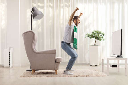 Excited young man with a scarf cheering and watching fotball on tv at home Imagens