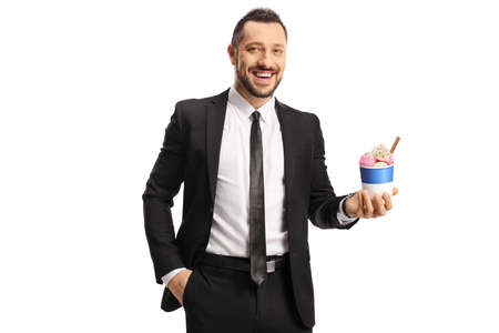 Man in a suit and tie holding ice cream in a paper cup and smiling Imagens