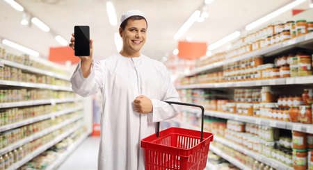 Man in ethnic clothes holding a shopping basket and showing a mobile phone inside a supermarket Imagens