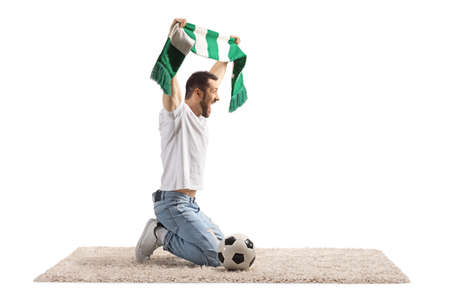Ecstatic young man with a scarf kneeling and cheering with a scarf and soccer ball