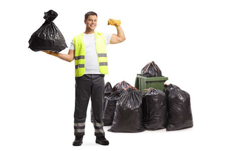 Full length portrait of a waste collector holding a bag and showing muscles in front of a bin Imagens