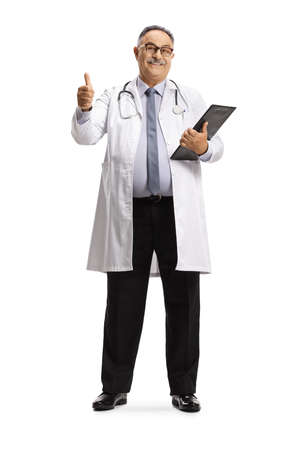 Full length portrait of a cheerful mature male doctor showing thumbs up isolated on white background