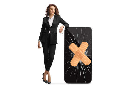 Full length portrait of a young businesswoman leaning on a cracked smartphone fixed with plaster