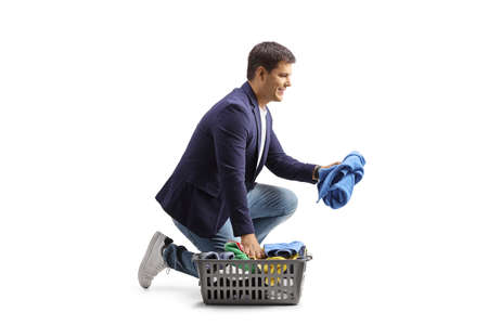 Man with a laundry basket kneeling and sorting clothes