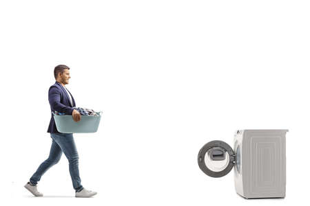 Full length profile shot of a man with a laundry basket walking towards a washing machine isolated on white background Imagens