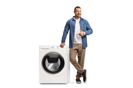 Young man leaning on a washing machine and pointing isolated on white background