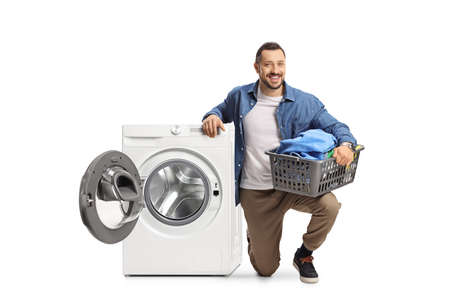 Young man kneeling nesto to a washing machine and holding a loundry basket isolated on white background