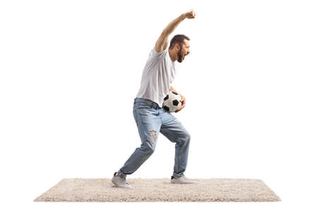 Young man with a soccer ball cheering and gesturing with hand Imagens