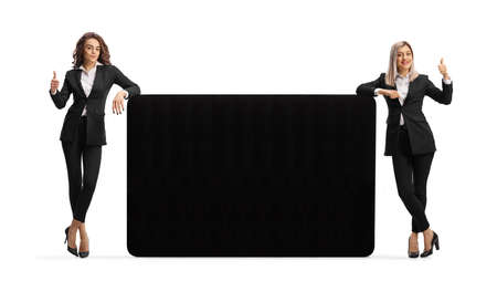 Young professional women leaning on a black panel and showing thumbs up