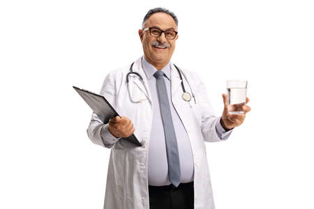 Mature male doctor holding a glass of water and smiling isolated on white background Imagens