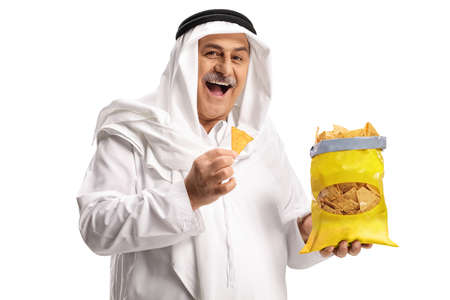 Cheerful mature arab man eating tortilla chips isolated on white background