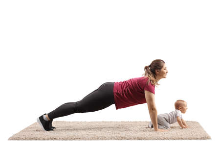 Young mother doing plank exercises with her baby crawling on carpet isolated on white background Imagens
