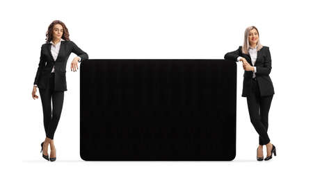 Two young businesswomen leaning on a big black panel isolated on white background