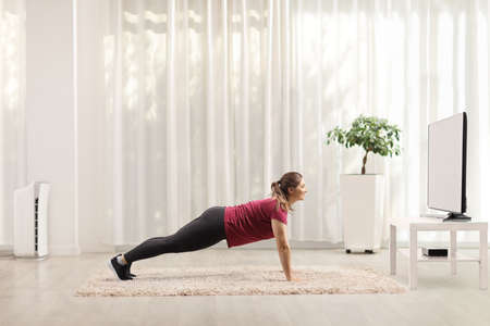 Young woman doing plank exercises in front of a tv at home