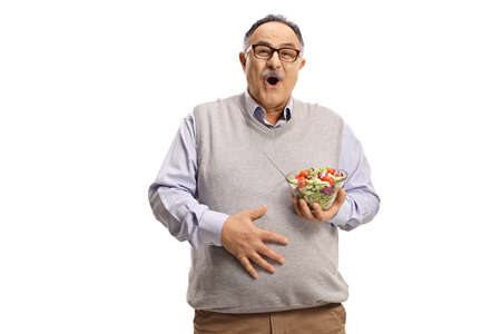 Mature man with a salad in a bowl holding his belly isolated on white background Imagens