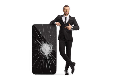 Full length portrait of a businessman leaning on a big smartphone with a broken screen and pointing isolated on white background Imagens