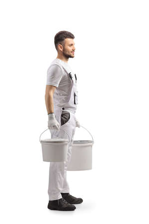 Full length profile shot of a painter in a white uniform carrying two buckets isolated on white background Imagens