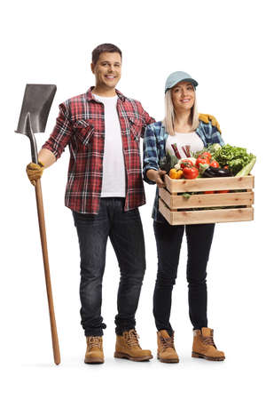 Full length portrait of a male farmer holding a shovel and a female farmer holding a crate with vegetables isolated on white background Imagens