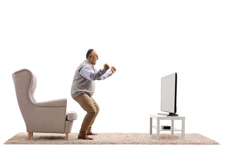 Full length profile shot of a mature man cheering in front of a tv solated on white background