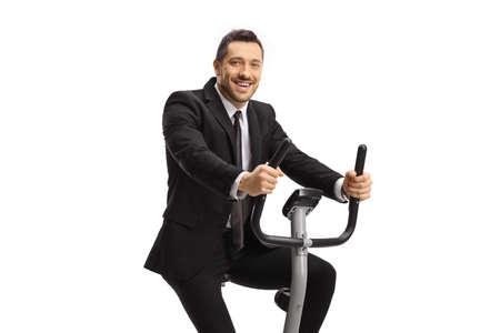 Businessman exercising on a stationary bike isolated on white background
