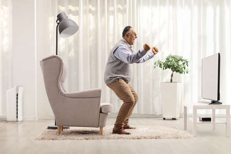 Full length profile shot of a mature man cheering in front of a tv at home