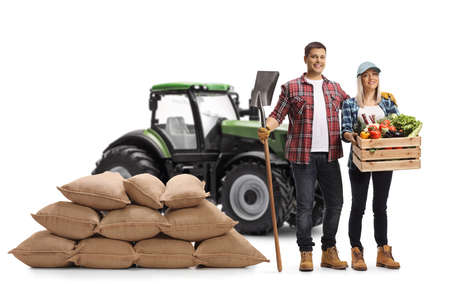 Full length portrait of young farmers with a tractor holding a shovel and a crate with vegetables isolated on white background Imagens