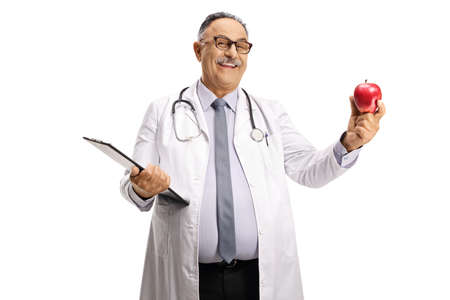 Smiling mature male doctor holding a red apple isolated on white background