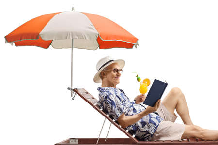 Elderly man enjoying on a sunbed with a book and a cocktail isolated on white background Imagens