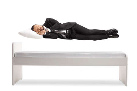 Man in a suit and tie sleeping and floating above his bed isolated on white background Imagens