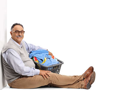 Smiling mature man sitting and holding a laundry basket isolated on white background Imagens