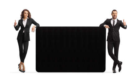 Professional man and woman leaning on a black panel and showing thumbs up isolated on white background