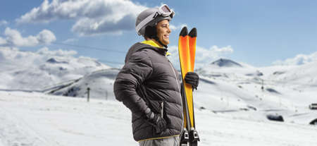Profile shot of a man holding skis on a snowy mountain
